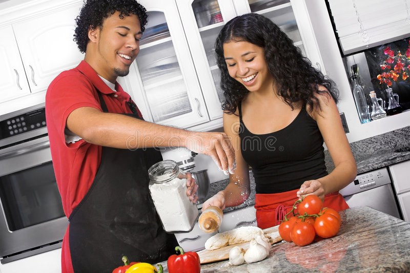 Couple cooking. Young diverse couple making pizza together in the kitchen royalty free stock photography