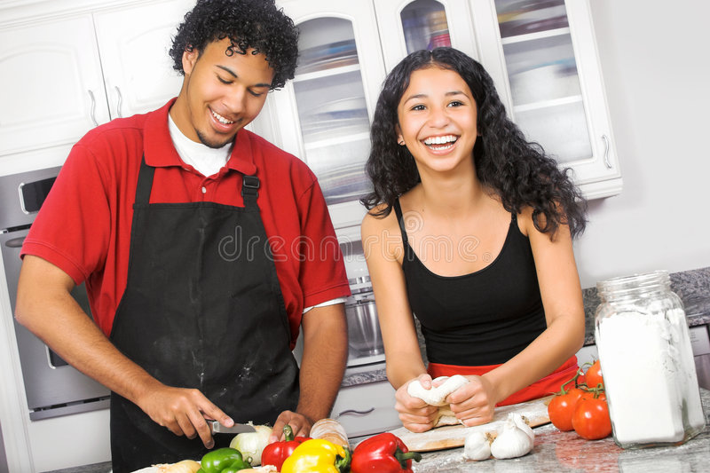 Couple cooking. Young diverse couple cooking pizza in the kitchen stock photo