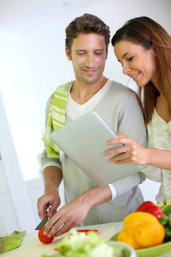 Free Couple Cooking And Using Tablet Stock Images - 30598334