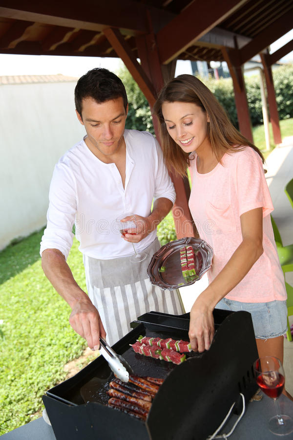 Couple cooking on barbecue. Couple cooking meat on grill at home royalty free stock photos