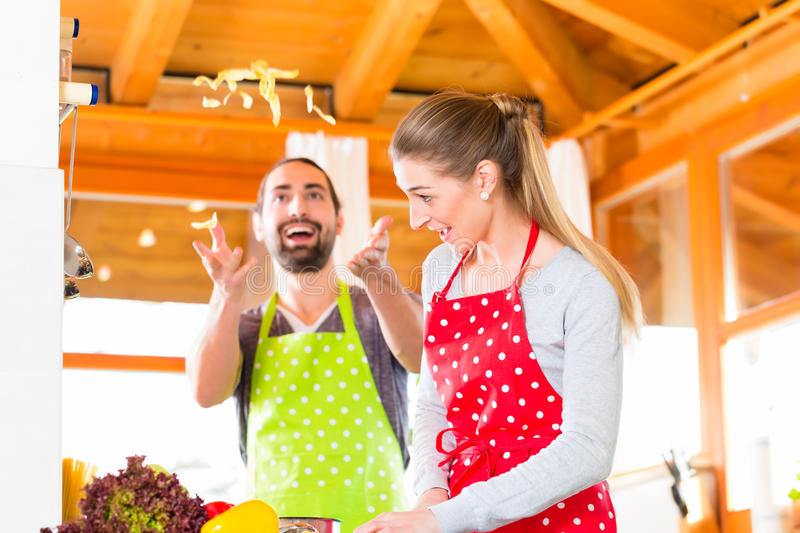 Couple cooking in domestic kitchen healthy food. Man and women preparing healthy meal in domestic kitchen at home stock photography