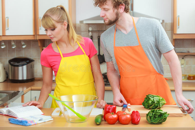 Couple cooking in kitchen reading cookbook. Happy young couple having fun in modern kitchen at home preparing fresh vegetables food reading cookbook looking for royalty free stock image