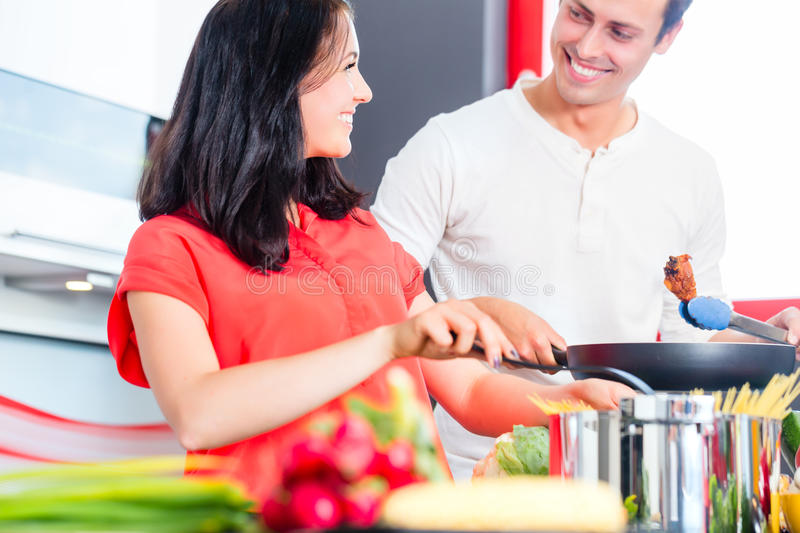 Couple cooking pasta in domestic kitchen. Woman and men cooking meat in domestic kitchen royalty free stock photography