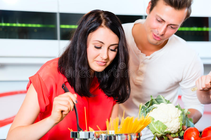 Couple cooking pasta in domestic kitchen. Woman and men cooking spaghetti in domestic kitchen royalty free stock photo