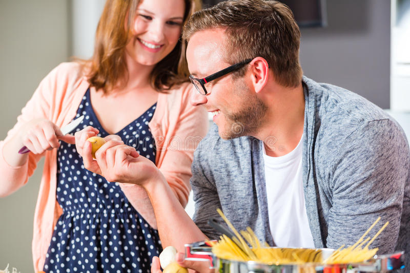Couple cooking pasta in domestic kitchen. Woman and men cooking spaghetti in domestic kitchen stock photography