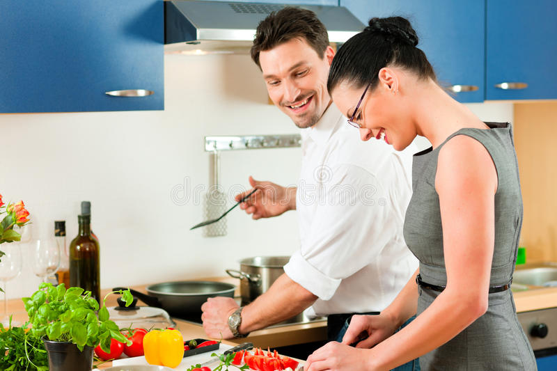 Couple cooking together in kitchen. Young couple - man and woman - cooking in their kitchen at home preparing vegetables for salad and pasta sauce royalty free stock photography