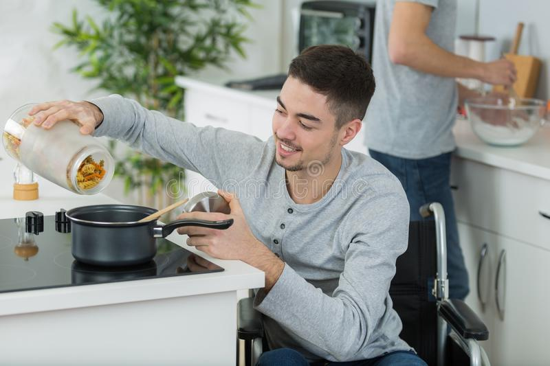 Couple cooking together - man disabled on wheelchair. Wheelchair stock photography