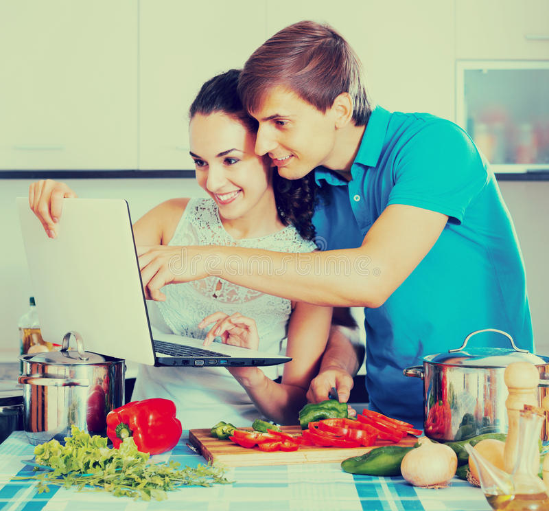 Couple cooking vegetables with laptop. Young men showing cooking housewife something on laptop screen stock photography