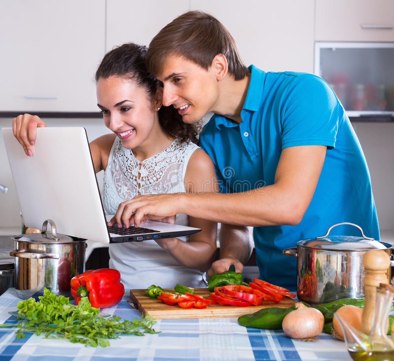 Couple cooking vegetables with laptop. Young smiling men showing cooking housewife something on laptop screen stock image