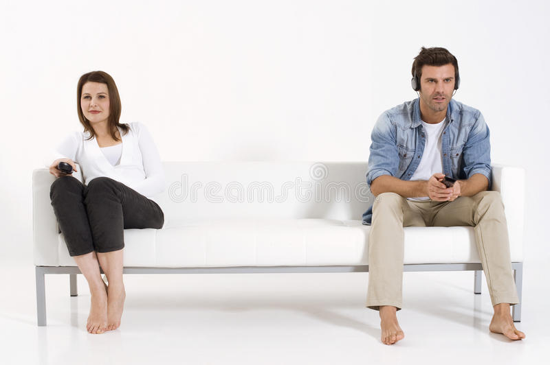 Couple on the couch watching TV. Separated couple on the couch watching TV royalty free stock photos