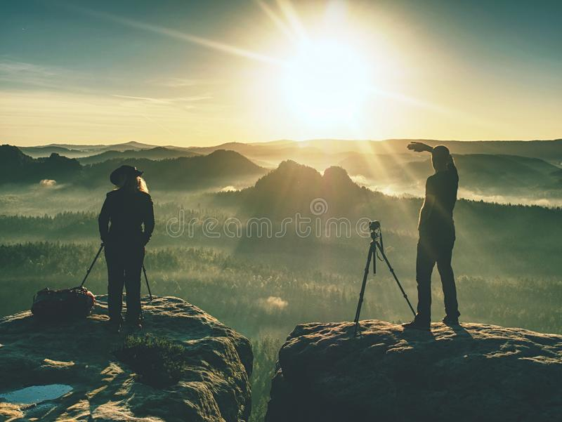 Couple of creative artists work and talk on exposed rock ledge stock image