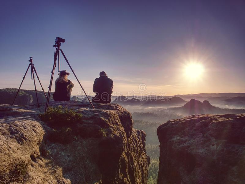 Couple of creative artists work and talk on exposed rock ledge. Couple of extreme creative artists work and talk on exposed rock ledge with beautiful view into stock photo