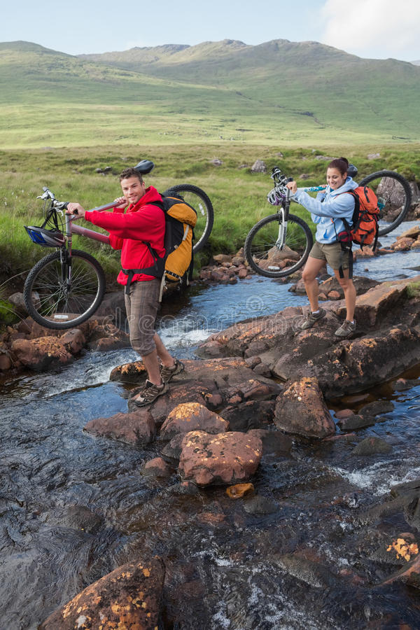 Couple crossing a stream holding their mountain bikes stock photography