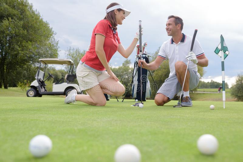 Couple crouching on golf course stock photo