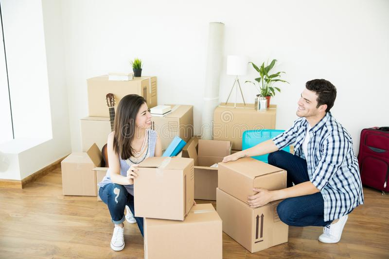 Couple Crouching While Stacking Cardboard Boxes In New Home. Happy mid adult men and women in casuals crouching while stacking cardboard boxes in new home royalty free stock images