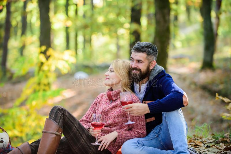 Couple cuddling drinking wine. Happy loving couple relaxing in park together. Romantic picnic with wine in forest. Couple in love celebrate anniversary picnic royalty free stock photos
