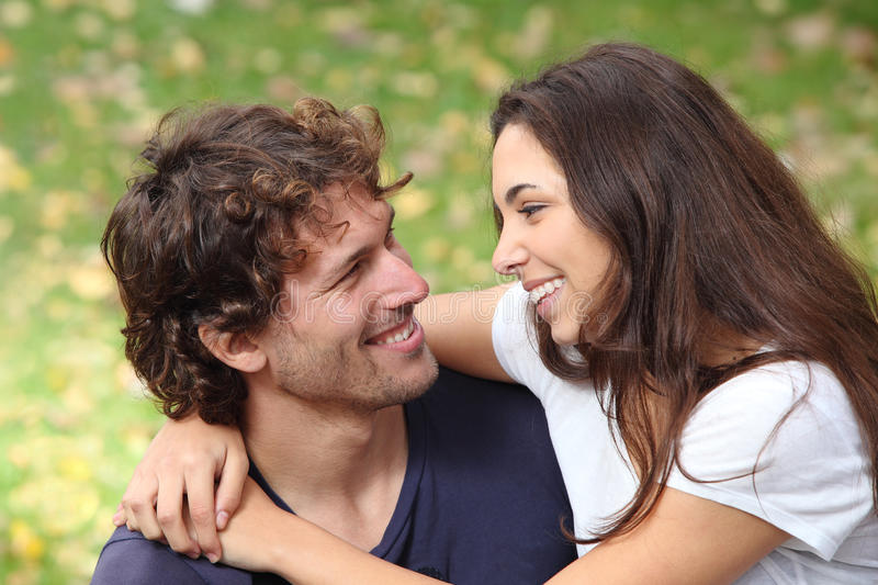 Couple cuddling and flirting in a park. With a green unfocused background royalty free stock photos