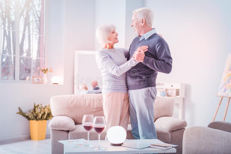 Couple of cute beaming pensioners celebrating their anniversary with wine stock photos