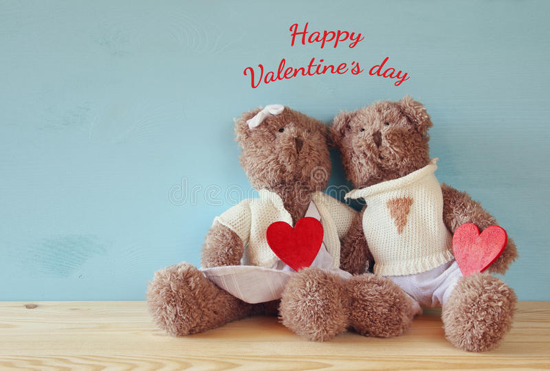 Couple of cute teddy bears holding hearts stock image
