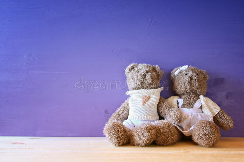 couple of cute teddy bears hugging on wooden table royalty free stock photography