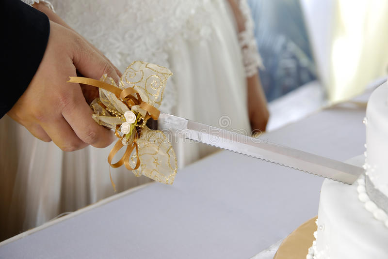 Couple cutting wedding cake. A young couple cutting cake at their wedding royalty free stock photos