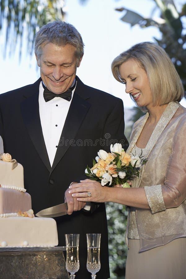 Couple Cutting Wedding Cake. Happy couple cutting wedding cake together stock images