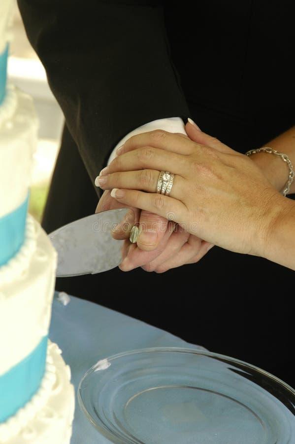 Couple cutting wedding cake stock image