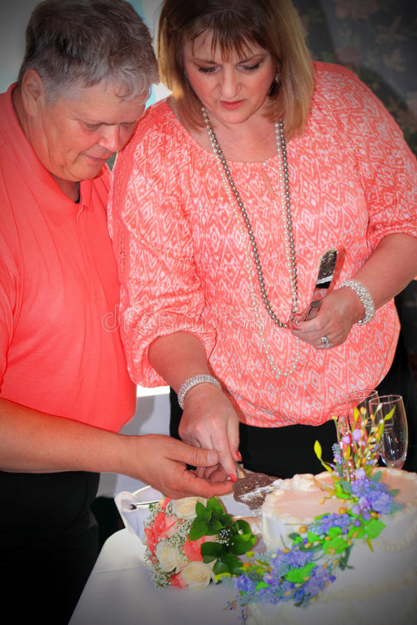 Couple Cutting Wedding Cake. An older couple standing cutting into a wedding cake. Shallow depth of field stock photo