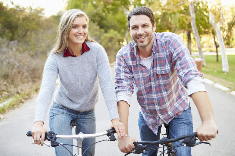 Couple On Cycle Ride In Countryside. Smiling royalty free stock photography