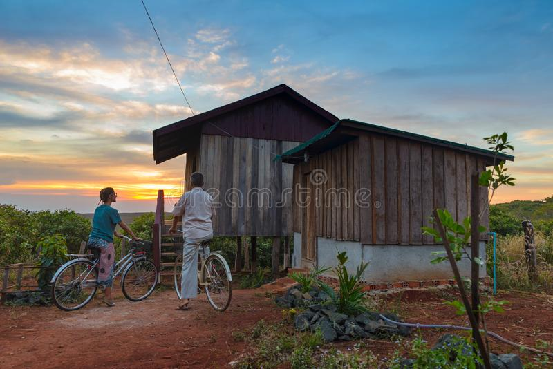 Couple cycling in the countryside, wooden cabin, dramatic sky at sunset, traveling wanderlust, outdoors activities royalty free stock images