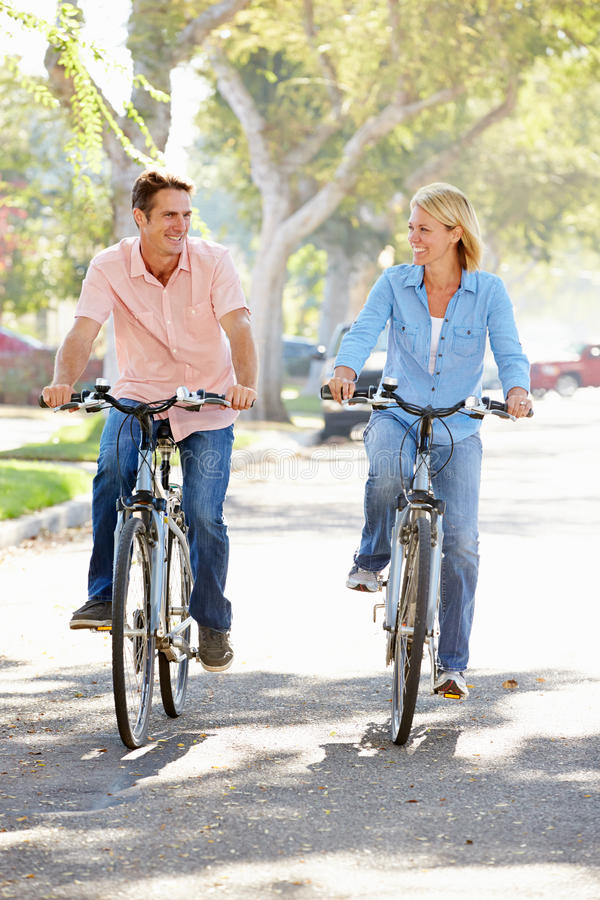 Couple Cycling On Suburban Street stock images