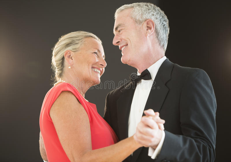 Couple Dancing Against Black Background stock photography