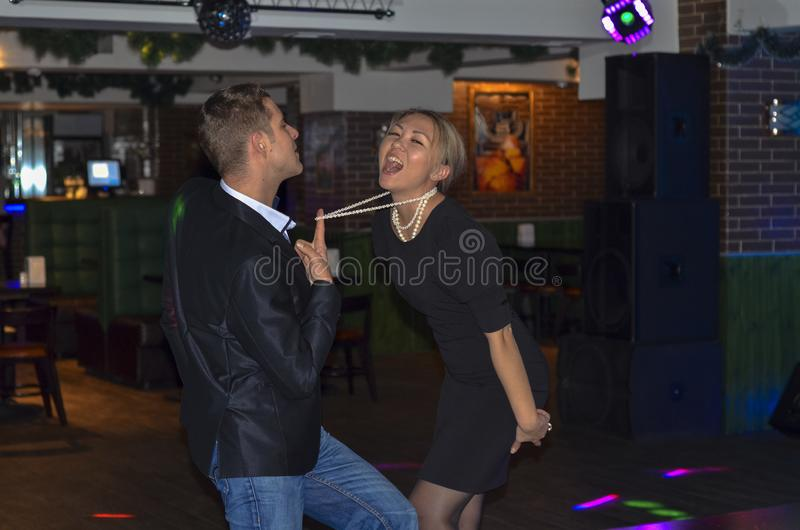 Couple dancing in a bar. Passionate dance. Party in the club. The guy pulls the girl by the beads royalty free stock images