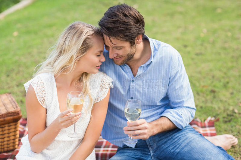 Couple on date holding white wine glasses stock photography