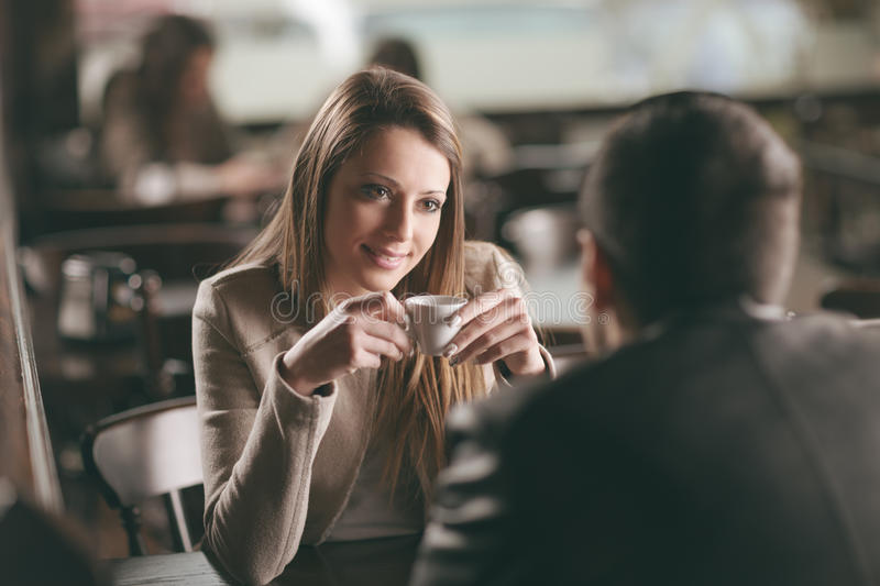 Couple dating at the bar. Young fashionable couple dating at the bar, she is having a coffee stock image