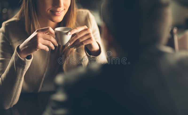 Couple dating at the bar. Young fashionable couple dating at the bar, she is having a coffee