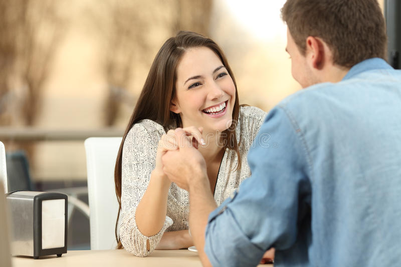 Couple dating and flirting in a coffee shop. Happy couple dating and flirting and holding hands together in a coffee shop with a sunset light outdoor in the royalty free stock images