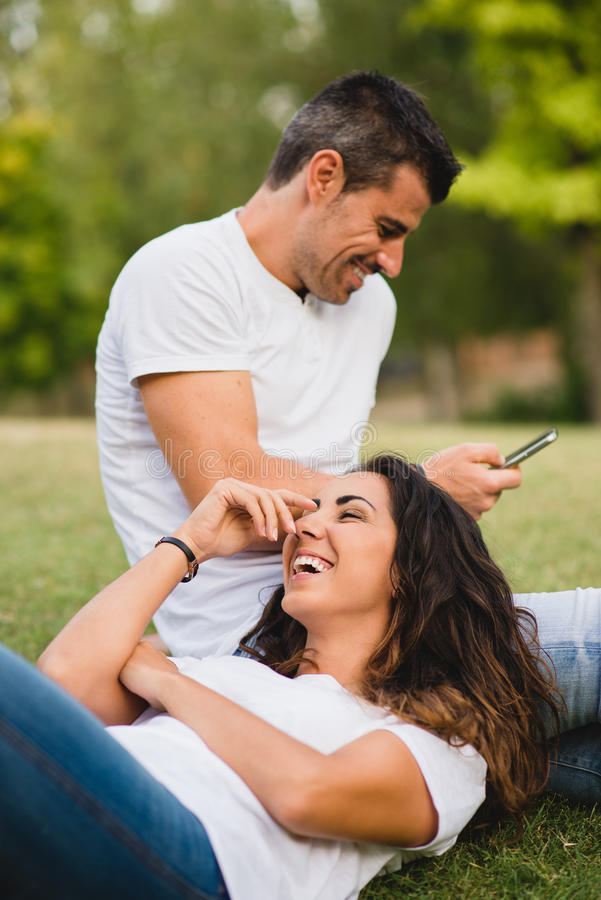 Couple dating and having fun. Loving young couple having fun and enjoying leisure on summer or spring at the park. Joyful men and women dating outdoor royalty free stock photo