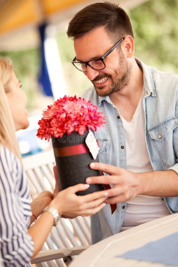 Young couple having romantic dating in the coffee shop, giving flowers stock photo