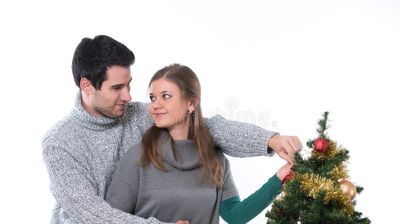 Couple decorating Christmas tree stock images
