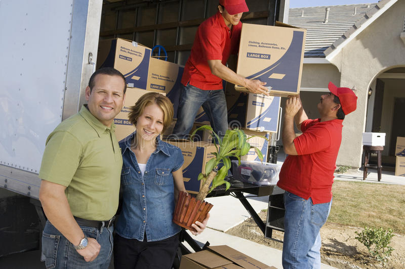 Couple With Delivery Men Unloading Moving Boxes From Truck. Happy couple with delivery men unloading moving boxes from truck into new house royalty free stock photos
