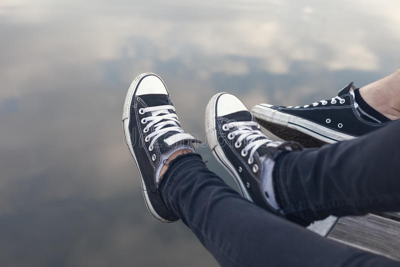 Couple des pieds dans des espadrilles détendant par l'eau photo libre de droits