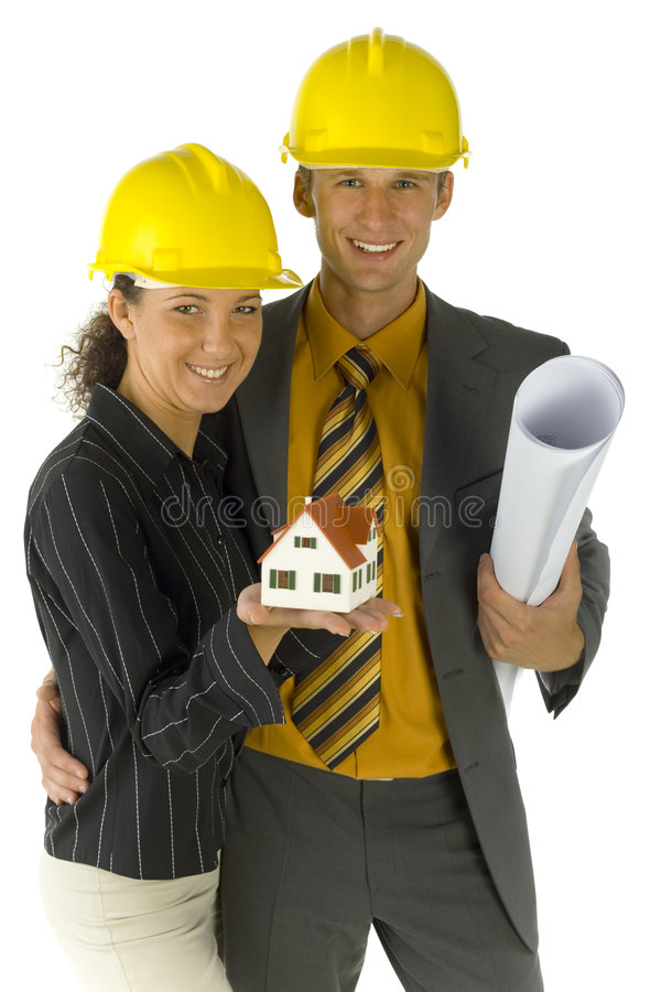 Couple of designers. Young, happy business couple in helmets. Man is holding some kind of paper, woman is holding house miniature. Looking at camera, front view royalty free stock photos