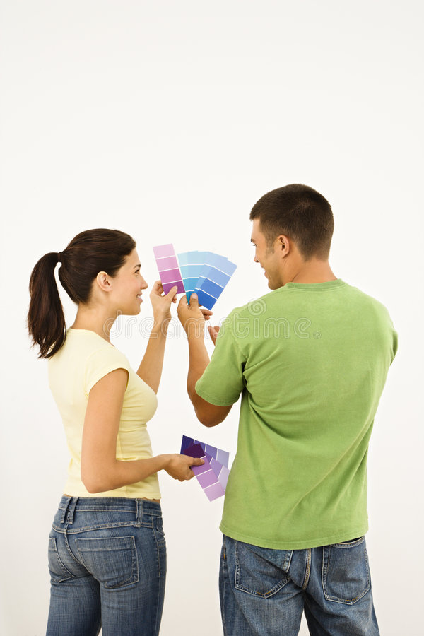 Couple designing home. Attractive young adult couple holding color paint samples up to white wall royalty free stock photography