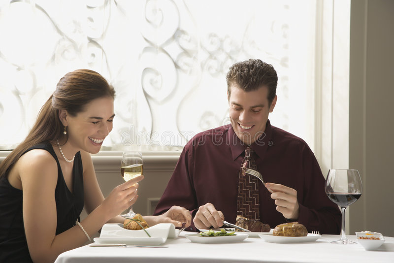 Couple dining at restaurant. Mid adult Caucasian couple dining in restaurant and laughing stock image