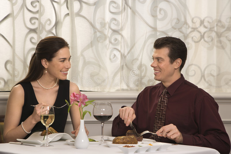 Couple dining at restaurant. Mid adult Caucasian couple smiling eating in restaurant royalty free stock image