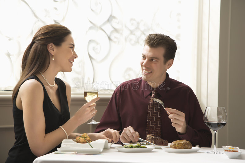 Couple dining at restaurant. Mid adult Caucasian couple dining in restaurant and smiling royalty free stock photos