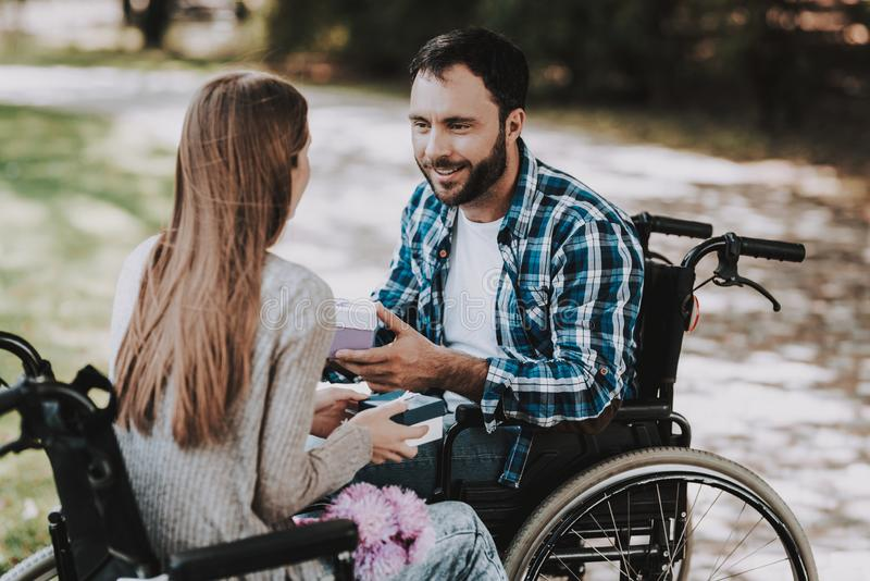 Couple of Disabled People Exchanging Gifts in Park. Disabled Young Man. Woman on Wheelchair. Date in Summer Park. Romantic Relationship. Recovery and stock photo