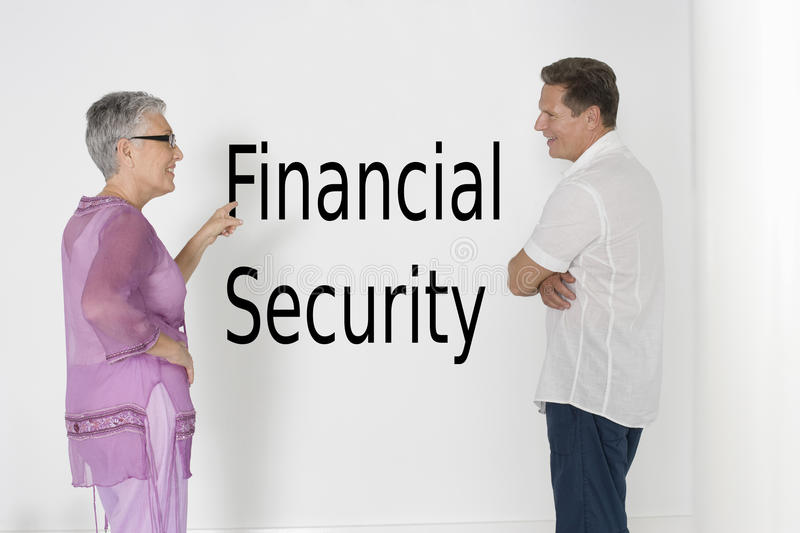 Couple discussing financial security against white wall with English text royalty free stock photography