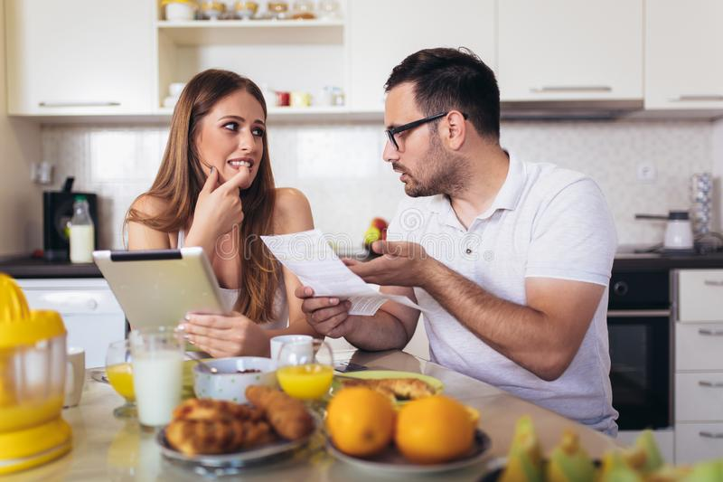Couple discussing about home budget in the kitchen royalty free stock photography